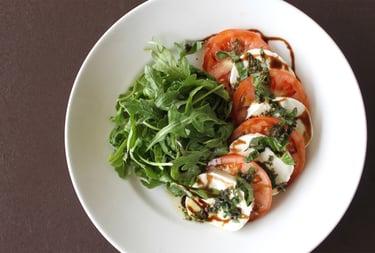 Caprese Salad with Sliced Mozzarella and Tomato on a white plate with arugula garnish