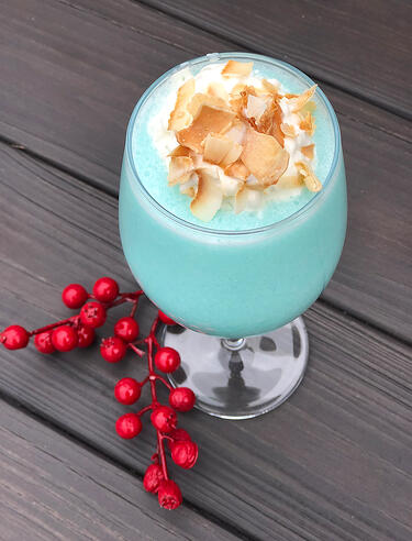 Light Blue Frozen Drink with Toasted Coconut Garnish in Tall Glass